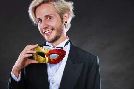 theatre masks: Holidays, people and celebration concept. Elegant young guy wearing suit white shirt bow tie and carnival venetian mask, on dark. Stock Photo