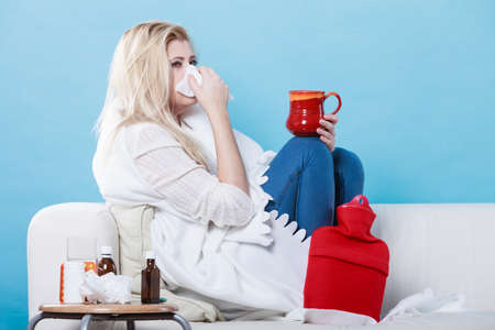 Sickness, seasonal virus problem concept. Woman being sick having flu lying on sofa holding mug cup with hot drink.