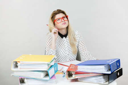 Woman sitting working at desk full off documents in binders thinking and working