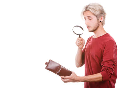 Broke young man holding magnifying glass looking for banknotes in empty wallet purse. Lack of money. Crisis and weak economy concept, isolated on white