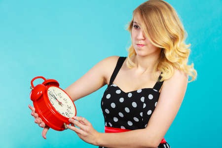Management time concept. Blonde emotional girl shocked expression wearing dotted dress with alarm clock on blue. Stock Photo