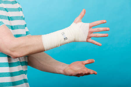 Fractures and dislocations concept. Part body male with hand in bandage. Helpful medication for painful palm arm of young man. Stok Fotoğraf