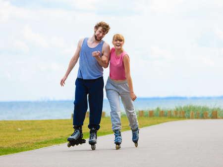 Vacaciones activas, ejercicios, concepto de relación. Joven mujer y hombre vestidos con forma deportiva, sosteniendo sus manos mientras que patinar juntos en el paseo.