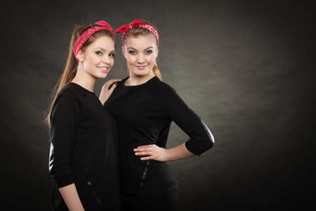 Love and affection in family. Blonde gorgeous sisters stylized on retro pin up vintage style. Two girls in red handkerchief smiling feel enjoyable happy. Stock Photo