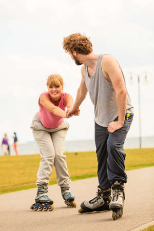 Active lifestyle people and freedom concept. Young fit couple on roller skates riding outdoors on sea coast, woman and man enjoying time together. Stock Photo