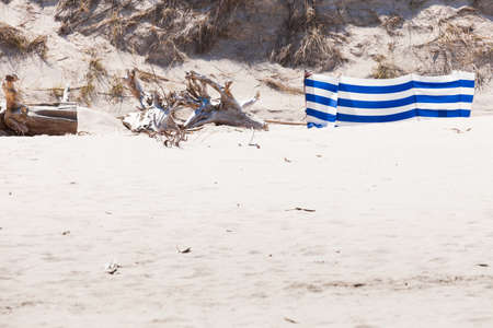 Blue and white windbreak on sandy beach durring sunny day. Summertime accessories, holiday essentials