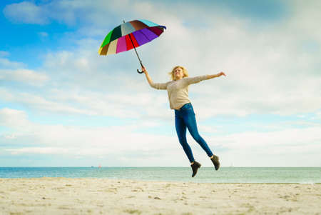 Happiness, enjoying weather, feeling great concept. Woman jumping with colorful umbrella on beach near sea, sunny day and clear blue sky