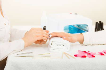 Woman hand on towel, preparing gel hybrid manicure, using nail polish remover to remove dust and oil from nails. Beauty wellness spa treatment concept