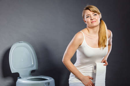Sick woman with hands pressing her crotch lower abdomen, holding paper roll in front of toilet bowl. Medical problems, incontinence, health care concept