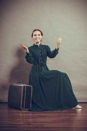 Woman retro style long dark green gown with old suitcase, vintage photo photo