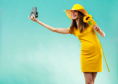 summer woman wearing yellow dress and hat with sunflower taking self picture with old vintage camera on vivid blue background photo