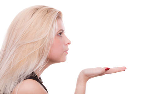 Gestures and human reactions concept. Coquet blonde woman sending air kiss on palm hand, profile view Stock Photo