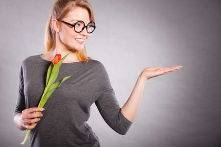 tenderly: Text space copy advertising concept. Young gorgeous lady with flower. woman holding red tulip making showing gesture.