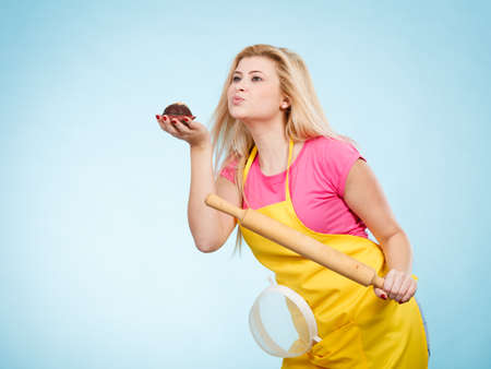 Baking tasty desserts sweets at home concept. Woman holding delicious chocolate cupcake, rolling pin and colander, wearing apron