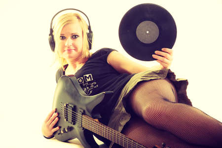 Music retro style. Young rock roll female star holds playing electric guitar surrounded by vinyl record. Classical audio collection. photo