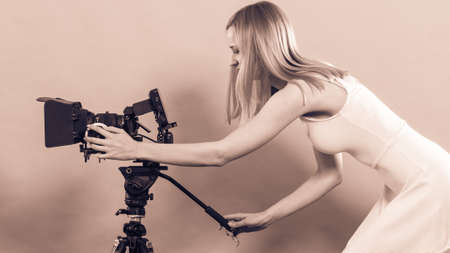Photographer girl shooting images. Attractive fashionable blonde woman taking photos with camera filtered photo Stock Photo