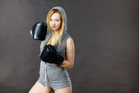 Young hooded woman fighting boxing. Blonde attractive girl wearing black punch gloves. Sport and fitness, power, exercising, on grey Stock Photo