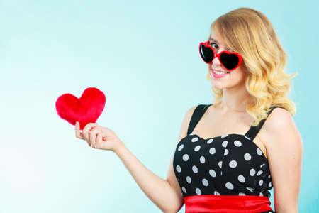 Woman blonde lovely girl wearing dotted dress sunglasses holding red heart love symbol studio shot on blue. Valentines day happiness concept