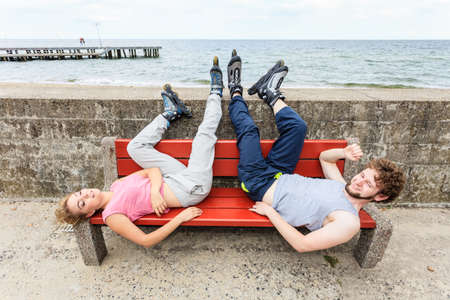 Young tired people friends in training suit with roller skates. Woman and man relaxing lying on bench outdoor. Stock Photo