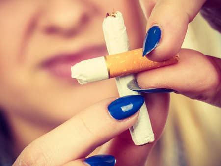 breaking: New Year resolutions, bad habits, unhealthy lifestyle concept. Woman breaking cigarette, getting rid of addiction