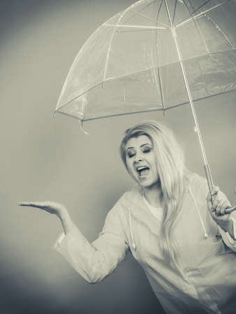 Woman wearing raincoat holding transparent umbrella checking weather if it is raining.