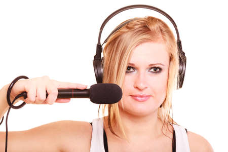 Music, passion concept. Studio shot of blonde young woman singing to microphone and wearing big headphones on her head, isolated portrait photo
