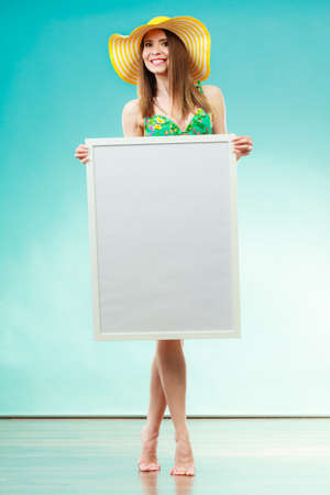 Holidays summer and advertisement concept. Woman wearing yellow hat and bikini holding blank presentation board. Female model posing in full length on blue background. photo