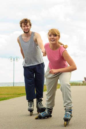 Vacaciones activas, ejercicios, concepto de relación. mujer joven vestida con ropa deportiva poniendo a su novio hasta qué patinar mientras mantiene su mano en el paseo