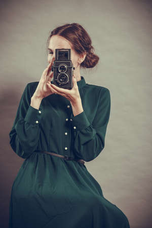 Woman retro style long dark gown taking picture with old camera, vintage photo photo