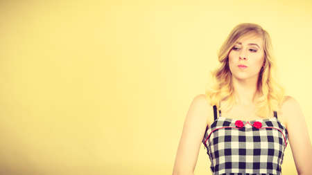 Young blonde attractive woman wearing checked top with red buttons making offended face expression being mad at someone. Studio shot on yellow background