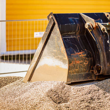 Detailed close up of excavator shovel in heavy industrial machine in sand.