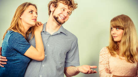 unfaithful: Bad relationships in triangle. Two beauty unhappy girls with sneaky cheating man.