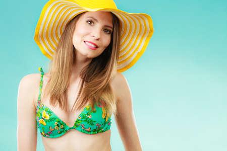 Summer holidays concept. Closeup woman in yellow hat bikini portrait on vivid blue background photo