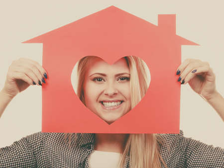 comfortable: Charity, real estate and family home concept - Happy smiling teen girl holding red paper house with heart shape, toned image