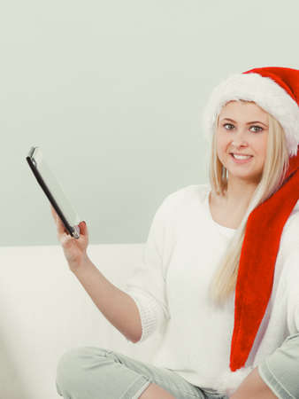 christmas spending: Online shopping, buying Christmas gifts on Internet concept. Woman in Santa hat sitting on sofa holding tablet browsing net.