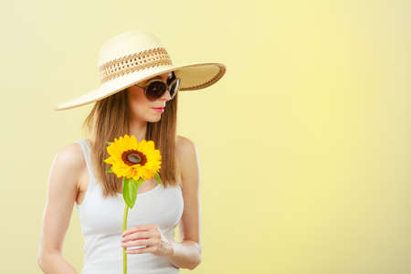 Closeup of attractive summer woman in sunglasses straw hat with sunflower in her hand on yellow background photo