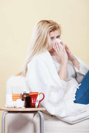 couch: Sickness, seasonal virus problem concept. Woman being sick having flu lying on sofa sneezing into tissue
