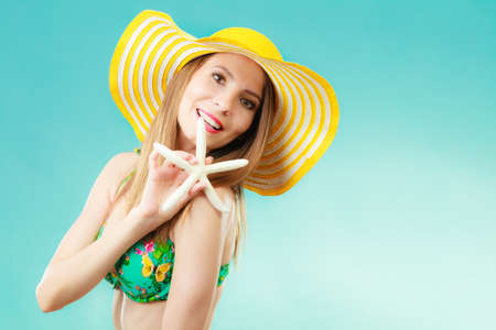 Summer holidays concept. Closeup woman in yellow hat bikini holding white shell starfish in hand on vivid blue background photo