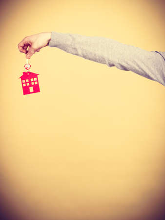 real estate sold: Closeup male hand holding new house key with red home shape. Real estate and housing concept.