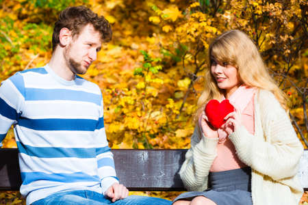 Accepting and sharing feelings. Confessing love and affection with romantic gesture. Positive reaction. Pair sit on bench in park woman present plush heart toy to man. Stock Photo