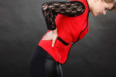 Health problems, strain on joints concept. Closeup of woman in elegant clothes suffers from backache Stock fotó