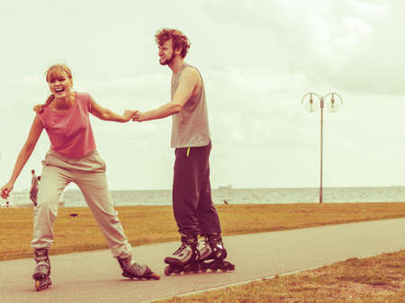 persuade: Active holidays, exercises, relationship concept. Young woman dressed in sports clothes putting her boyfriend up to do rollerblading while holding his hand on promenade Stock Photo