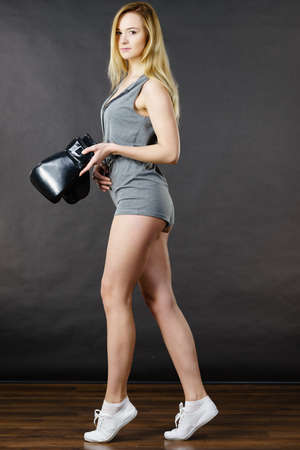 Blonde sporty woman holding black boxing gloves after fight. Studio shot on dark background.