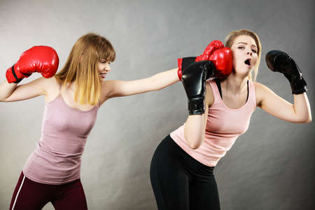 Agressive women having argue fight wearing boxing gloves, female friend being scared. Violance concept. Stock Photo