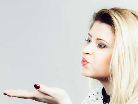 Coquet blonde woman sending blowing air kiss. Romantic gestures concept. Studio shot on grey background.