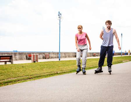 Las personas activas amigos mujer y hombre en traje de entrenamiento de patinaje.