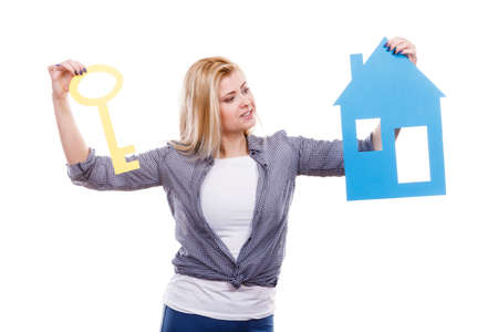 Dream about stabilization, plans for future. Blonde girl holding blue paper house model and yellow key cutout. New flat apartment. Isolated on white