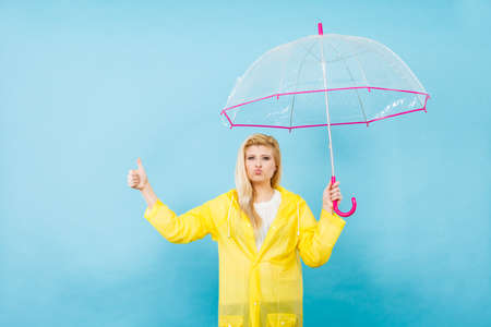 Blonde woman wearing yellow raincoat holding transparent umbrella checking weather if it is raining showing thumb up gesture Stock fotó - 85201383