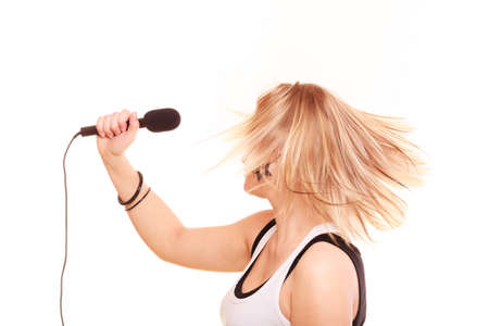 Karaoke, music, singer concept. Blonde woman singing to microphone, performance of young star, studio shot isolated Stock Photo