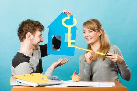 Real estate ownership finance concept. Just married designing their house. Young couple man and woman holding cutouts of key and home. Stock Photo